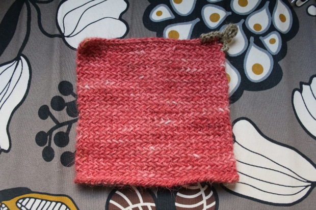 Pink knitted potholder with crocheted hook loop