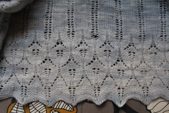 Moth hole in a pale blue knitted Icarus shawl