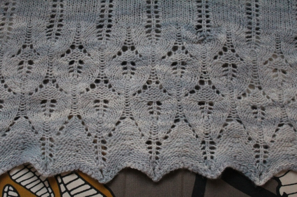 Pale blue knitted Icarus shawl with mended moth hole