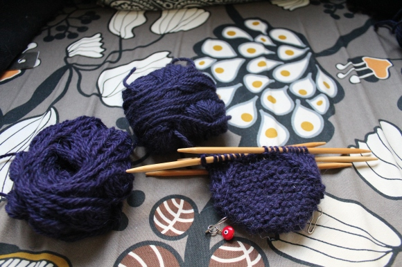 A skein of purple yarn and a skein of purplish blue yarn next to the start of a mitten