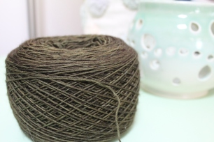 Cake of olive green yarn dyed by Gherkin's Bucket