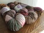 Three skeins of DK weight Less Traveled Yarn in Turning Leaves colorway