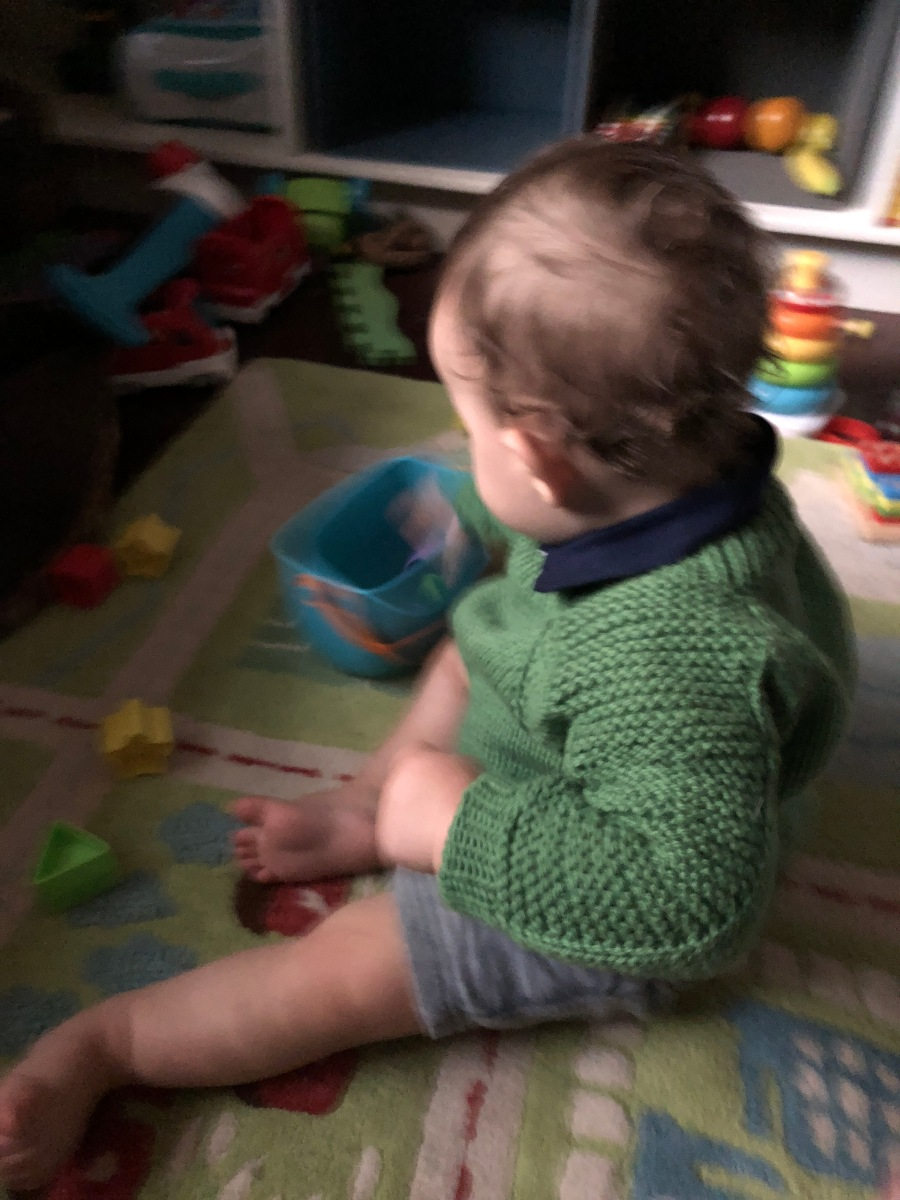 Baby playing on a colorful rug and wearing a green Flax pullover sweater