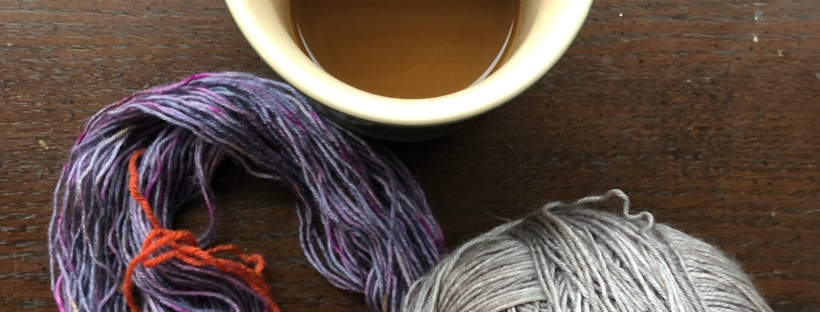 Purple and gray yarns from Less Traveled Yarns and a coffee mug