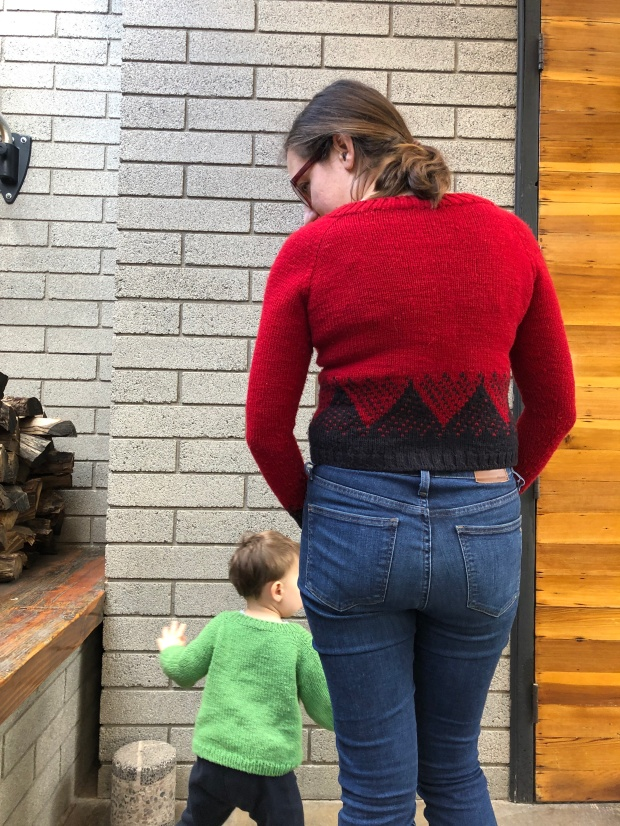 Back view of a woman wearing a red handknitted sweater with a geometric black mountain pattern with a child running behind her