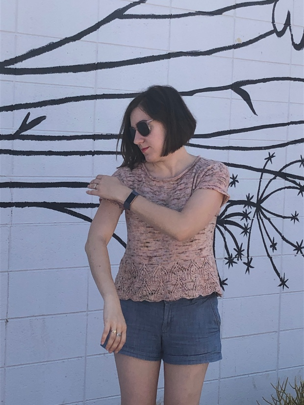 Woman in a pink knitted Tegna top smoothing her sleeve in front of a white wall painted with the outlines of wildflowers