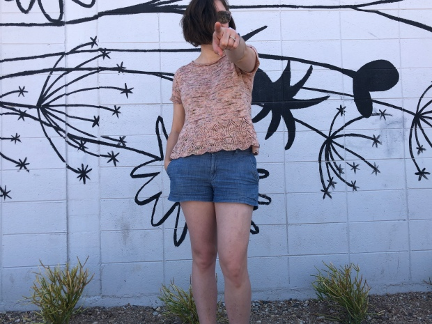 Woman wearing a pink knitted Tegna top and pointing at the photographer in front of a white wall painted with the outlines of wildflowers