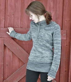 Image of a model wearing the Ease pullover by Alicia Plummer in front of a barn door, image copyright Alicia Plummer