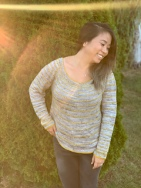 Image of Tina Tse wearing her Golden Horizon Sweater in a garden as sun flashes across the camera lens, image copyright Tina Tse