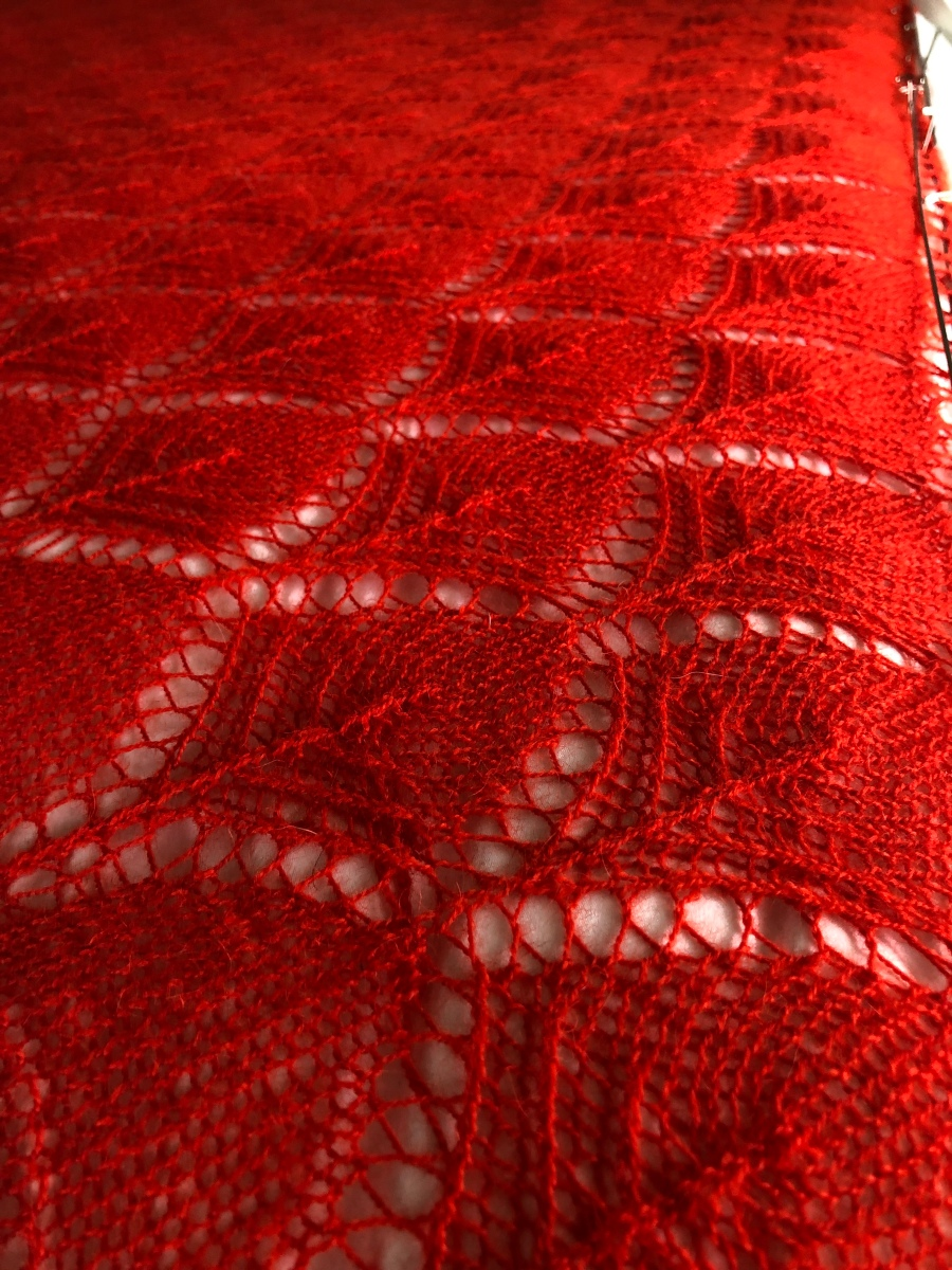 Flower basket motif in orange-red laceweight blocked against a white sheet