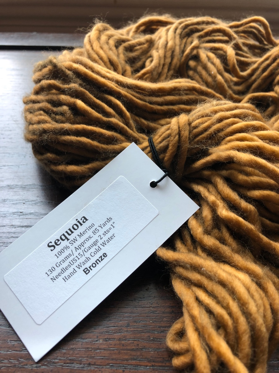 Untwisted hank of bulky Baah! Sequoia yarn in Bronze on a dark wood surface