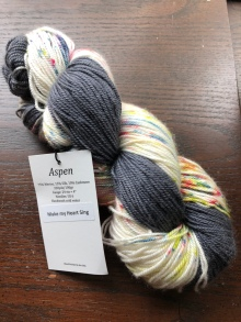 Baah! Aspen yarn in Make My Heart Sing, a variegated gray and speckled cream multi, on a dark wood background