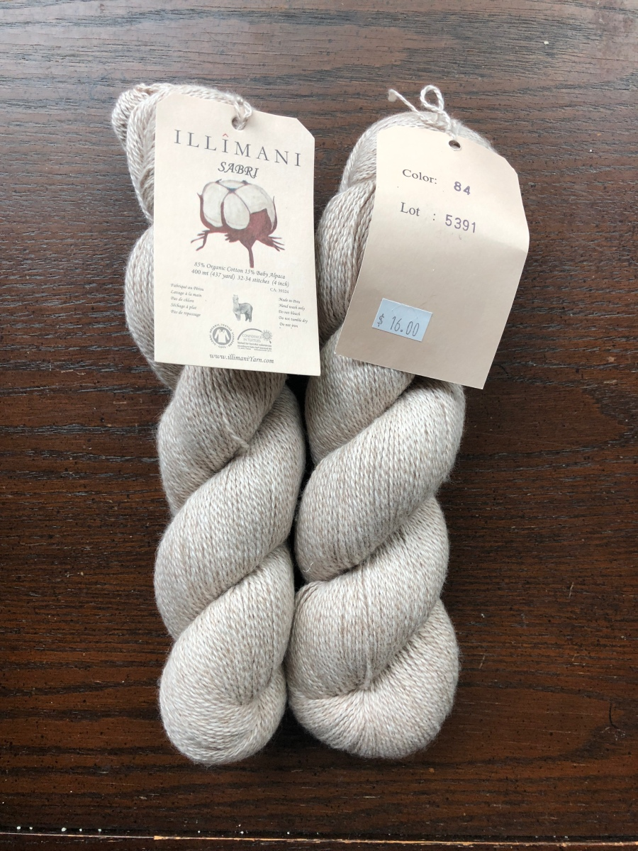 Illimani fingering weight cotton and alpaca blend yarn in pale fawn on a dark wood background