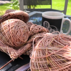 Cakes of speckled peach yarn on a glass table with a BFI mug