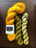Onyx Fiber Arts Mohair in Mari, a bright gold, with mini skeins of Baah! La Jolla in greens, on a dark wood background