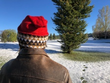 Woman wearing an Embrace My Inner Pixie hat in red with a black, gold, and white geometric brim against a backdrop of trees and light snow