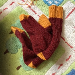 Maroon and gold Classic Socks folded up against a child's play rug