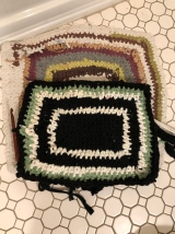 New bath mat crocheted out of recycled t-shirt fabric on top of old, ragged bath mat