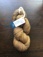 Amores Yarn Studio Raíz sock yarn in spices, a warm gold, on a dark wood background