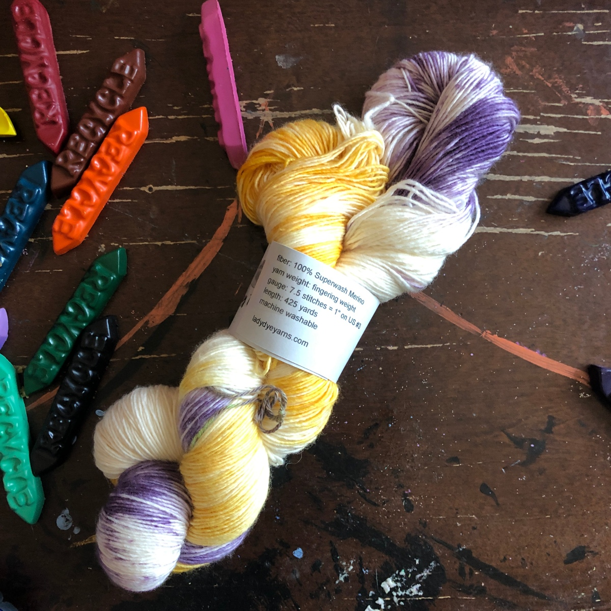 Lady Dye single-ply fingering weight in purple and yellow on a table with crayons