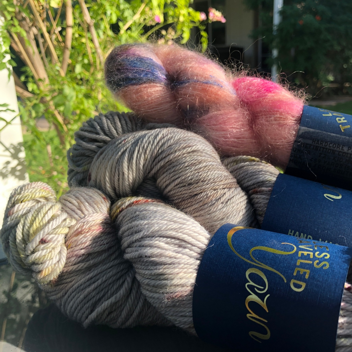 Three skeins of Less Traveled Yarn in smooth gray and fuzzy pink against a backdrop of vines
