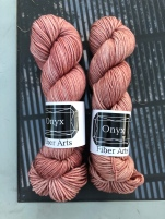 Onyx Fiber Arts Worsted in Sophia. a soft pink, on a glass table reflecting a vine-covered pergola