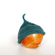 Image of a Little Sprout Hat by Heidi Gustad of Hands Occupied modeled on an onion with a smiley face drawn on, image copyright Heidi Gustad