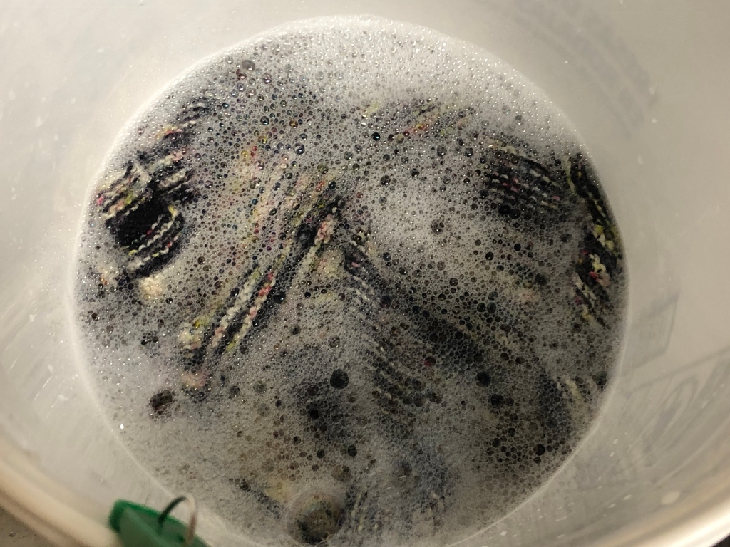 Knitted fabric partially obscured by bubbly water